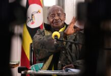 museveni standing open-roofed cars